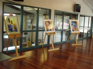Paintings set up on easels.
